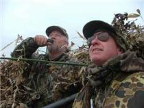 "Hunting & fishing guide Steve McCadams (left) calls at a high duck with his ""baby brother"" Kevin, a tennis pro, at his side."