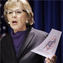 "Senator Barbara Boxer holds up ""Liberal Hunting Season"" sticker at a press conference"