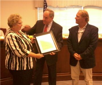 Cleveland City Mayor Tom Rowland (center) presents Della Renner (left) and her son, Rob Renner (right) with a Resolution Honoring the Service of Bruce Renner.