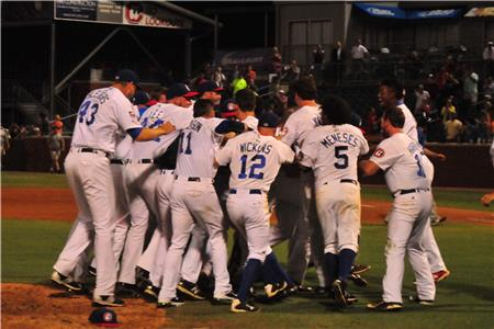 Players mob Jason Wheeler after the third out of the final game.