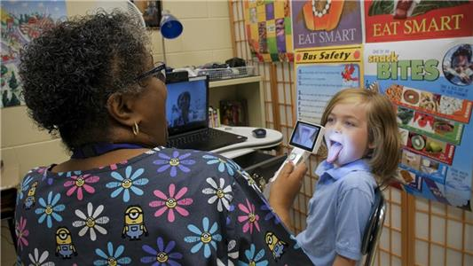 Nurse Regina Hickman examines Trenton Brumfield's throat during a telemedicine visit with Yvonne Hughes, NP at Orchard Knob Elementary School