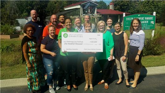 Brenda Reid, Media & Community Relations manager for Publix Super Markets Charities, presents a $100,000 donation check to Gina Crumbliss, president & CEO of the Chattanooga Area Food Bank, and other Food Bank employees.