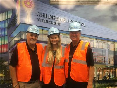 Jim, Alexis, and Steve Frost are pictured in front of a rendering of the new Children's Hospital at Erlanger
