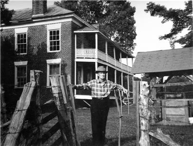 Charlie Harper poses in front of house at Broomtown Valley built in 1841