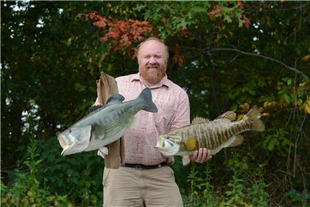 Mike Jolley holds two record bass replicas