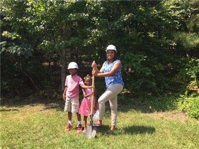 Janelle and her two children breaking ground on their new Habitat home