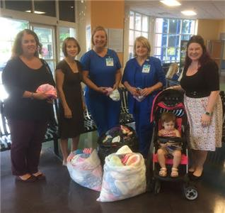 NICU Noggins Knitalong representatives at Children's Hospital with bags full of hand-knit hats.  From left, Melanie Lowery, Tiffany Weeks, Anne-Miele Leyssens, Cheryl Yeoman, Madelyn Hamilton, and Dana Hamilton.