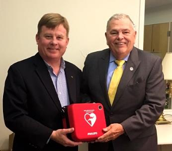 Mark Kimball, CEO of Erlanger Murphy Medical Center, delivers an AED to Elmer Wilson, Jr., president of the Board of Directors for Peacock Performing Arts Center