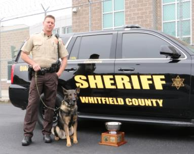 "Whitfield County Sheriff's Office Deputy Todd Thompson and his K9 partner Eddy pose beside their vehicle with the trophy they won after being named ""Top Dog"" at a regional contest held in Rome earlier this year. The strong showing earned the crime-fighting duo an invitation to the United States Police Canine Association Nationals in Huntsville, Ala."