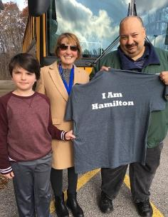 Charlie Baker, a sixth-grader at Signal Mountain Middle/High, and District 2 Board Member Kathy Lennon present Jonathan McKenney with the I Am Hamilton t-shirt.