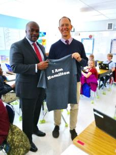Dr. Bryan Johnson, superintendent of the Hamilton County Schools, presents John Echols with the I Am Hamilton T-shirt