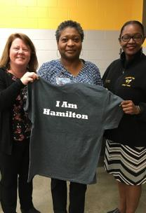 Jill Levine, chief of Opportunity Zone for Hamilton County Schools and Tiffany Earvin, principal of Orchard Knob Middle present Tanya Turman with the I Am Hamilton t-shirt