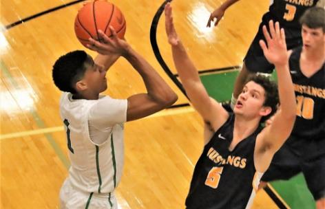 Noah Dupree of Walker Valley gets a hand in the face of East Hamilton's Jamaal Walker's Tuesday in a basketball showdown at East Hamilton. The two  District 5-3A rivals battled into overtime before the Hurricanes pulled out a 63-58 victory.