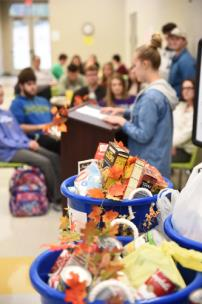 Food items collected for the Marion County Food Bank flank Cassidy Kennemore as she reads her poem to fellow students during Bread and Words