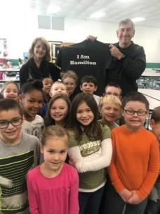 Jacquie Hauth, principal of North Hamilton County Elementary and kids in Ms. Dent's first-grade class, present Joe Barbeauld with the I Am Hamilton T-shirt