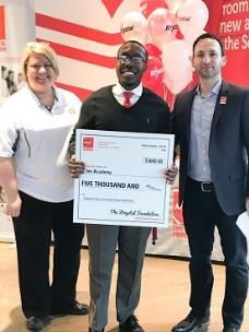 Roy Collins, band director at Tyner Academy, accepts the $5,000 check for band instruments for his program from Paul Macaluso, Krystal CEO and president of The Krystal Foundation, and Lyticha Jennings, district manager for Krystal