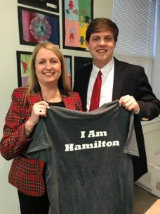 "Tucker McClendon, board member representing District 8, presents Sherri Ford with the ""I Am Hamilton"" t-shirt before the December Board of Education meeting"