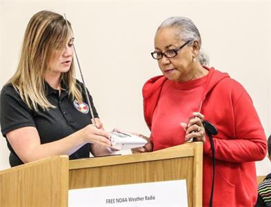 Amy Ramsey of Whitfield Emergency Management Agency offers advice to a local resident on the proper use of a weather radio given away in November by the agency