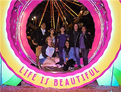 Calvin Huang, center, the first recipient of the Life Under the Wheel grant, chose Life Is Beautiful as the music festival he wanted to attend. UTC's Evan Gross, standing far left, and his business partner, Elizabeth Pikaart, kneeling left, created the Life Under the Wheel program.