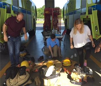 Nick Montgomery, teacher; Glenn Perry, assistant principal; and Virginia Jackson, a teacher at Brainerd High Future Ready Institute of Aviation try on firefighting gear at the Chattanooga Airport during an externship visit to learn more about the world of aviation