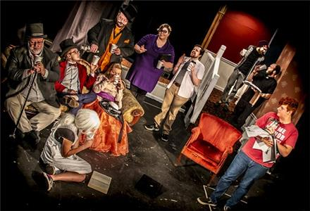 In background, from left to right:  Greg Guinn as the villain actor, Kelsey Jordan as the playwright, Dillon Hartley as the director, Gavin Russell as the techie, Zachery Green as the stage manager. Seated, left to right: Michael Tate, Keegan Westra, Sarah Lee, Madeline Cepeda (on floor) as actors in the show within a show. Jack Pressley (right) as the intern.