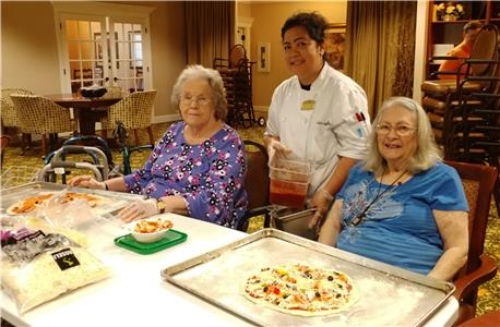 Morning Pointe of Hixson Food Services Director Yolanda Gilbert and residents Vera Sachleben and Lavelle Burnett showcase the homemade pizzas they made as part of Ms. Gilbert's monthly baking club.