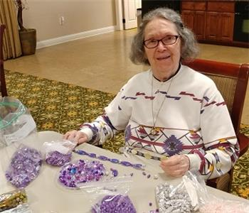 "Morning Pointe of Hixson resident Marti Landis strings together a necklace, just one of the jewelry items that will be sold at the ""Movie Night at The Barn"" event at The Barn in Hixson on Sept. 8."