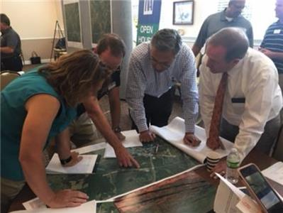Georgetown property owner Greg Vital and Rep. Mike Carter discuss the route of a proposed right of way through Mr. Vital's property with TVA official Thursday in Georgetown.