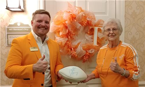 Morning Pointe of Hixson Executive Director-in-training Cody Harvey and resident Pat Arnold show off their Vol pride—and a football signed by Peyton Manning