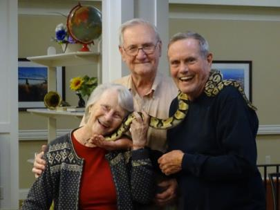 Morning Pointe of Chattanooga – Shallowford residents Nancy Kimbro and Tom Donovan cuddle up to Kaa, the Chattanooga Zoo's balboa python, while resident Clyde Edwards looks on. Ms. Donovan and Mr. Edwards are longtime supporters of the zoo and have a history of volunteering there.