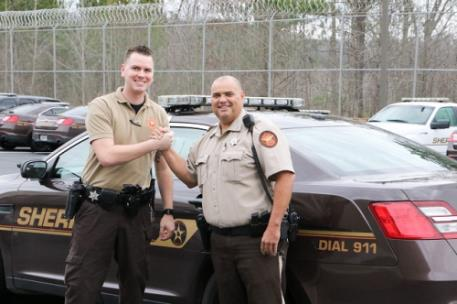 Whitfield County Sheriff's Office Deputies Jeffrey Diak (left) and David Headrick shake hands next to Headrick's patrol car. Diak will be giving a kidney to Headrick, who is currently undergoing dialysis three times a week to stay alive due to an auto-immune disorder.