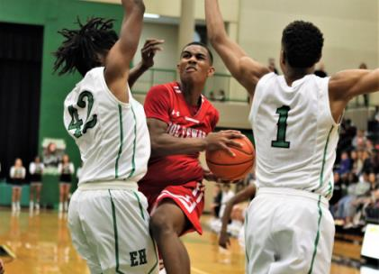 Greyson Wood, who scored a game-high 15 points, tries to get past East Hamilton defenders, Deaunte Crawford (42) and Jamaal Walker (1) Friday night during the teams' District 5-3A basketball game. The Hurricanes won, 52-51, and kept sole possession of first place(6-0) in the district standings.
