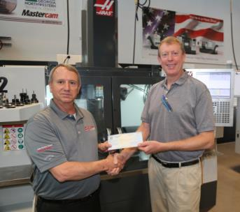David Aycock, left, presents a check to Philip Shirley for the Precision Machining and Manufacturing program on the Whitfield Murray Campus