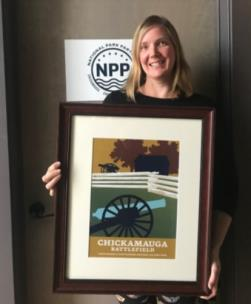National Park Partners executive director with framed artwork from the Centennial Series