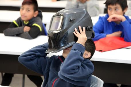Dalton Public Schools student Jairo Lara tries on a welding helmet at the GNTC Whitfield Murray Campus on Friday, Nov. 15. He and his fellow fifth graders from across the DPS system toured GNTC's newest campus through a partnership with United Way.