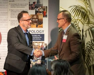 Dr. Jeffery Sargent, department chair, congratulating Dr. Mike Hayes, right, for being named Department Alumnus of the Year for the behavioral and social sciences department
