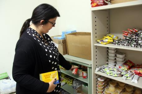 Special Populations Assistant Madison Hopper stocks one of the shelves in the GNTC Food Pantry on the Floyd County Campus