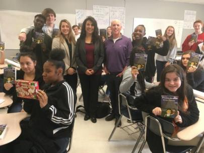 Haven Caylor-Brown, Ed.D., and his class show off their readers purchased with grant funds.  Joining the class to share in the books and some Little Debbie snacks are Brittany McKee and Claudia Thompson from McKee Baking.