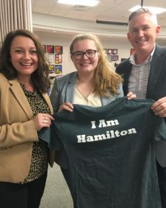 Blake Freeman, director of Future Ready Institutes for Hamilton County Schools; and Amanda Baron, Computer Science teacher and lead teacher at the Institute of Engineering and Computer Science at Red Bank High, present the shirt to Lily Akins.