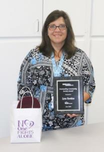 "Lynn Hawkins stands with a plaque she received after being named one of the eight finalists in the ""Drive It Forward"" contest sponsored by Mountain View Nissan in Dalton. Ms. Hawkins, who works in the Whitfield County Tax Commissioner's Office, is holding one of the Bags of Hope that her organization, Sassy's Hope, hands out to area cancer patients."