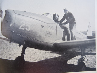 World War II promotional photo of pilot receiving training instructions