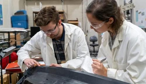 IACMI's Sean Lee and Tessa Patton work on the composite liftgate created for Volkswagen in their lab in the Science Engineering Research Facility