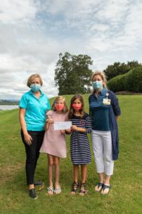 Jennifer Nicely, CHI Memorial Foundation president, on left, and Janelle Reilly, CHI Memorial market CEO, right, accept the donation from Olivia Atchley (left center) and Audrey Gibler (right center)