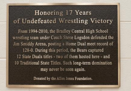 A special plaque placed in Jim Smiddy Arena at Bradley Central High School by the Allan Jones Foundation commemorates the Home Dual meet record of 128-0 that took place at the school from 1994-2010 under Wrestling Coach Steve Logsdon.