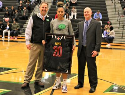 Madison Hayes, center, was presented with a framed McDonald's All-Star jersey during halftime of the boys' game Thursday night at East Hamilton High School. Shown with Hayes are school principal Brent Eller, left, and head girls basketball coach Hunter Gremore, right. Hayes will play on the East team at the McDonald's All-Star game on April 1st in Houston. The jersey will hang there at the high school.