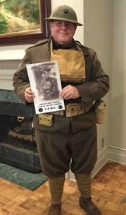 "Louis Varnell, dressed as a WWI soldier, gave a presentation on WWI – The Battle of Belleau Wood. His uniform includes gas mask around neck; canteen;  pants 'bloused in' with leg wraps: and uniform color ""Olive Drab"". He is holding a photo of his great-grandfather, who survived WWI and lived into his late 80's."