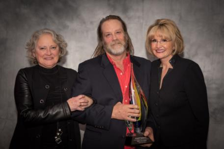 Pictured, are Cindy Bacon (left) and Phil Bacon (center), receiving the FASTSIGNS Award at the 2020 FASTSIGNS International Convention presented by Catherine Monson, CEO of FASTSIGNS International Inc. (right).