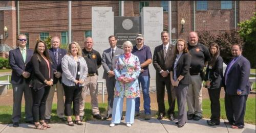 Conasauga Veterans Court team members stand in front of the Veterans Memorial near the Whitfield County Courthouse, including (from left, front row) Candice Groce, Leah Ozment, Judge Cindy Morris, Jennifer Richardson, and Christina Curtis; (back row) P.J. Hemmann, Kelly Johnson, Tim Bell, Christopher Tucker, Ray Figg, Todd Breitmann, Jeremy McMillan, and Geoff Bard.