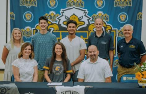 "Jada Mullins front row center, is shown at her signing ceremony with family, friends and former coaches. Mullins, a 6'1"" middle blocker from Berean Christian School has signed to continue her collegiate career with the University of Tennessee Chattanooga volleyball team."