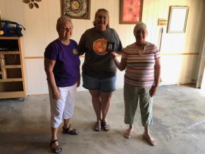 Gamma Chapter members Judy Bullington (right) and Chris Hockert (left) presented Andrea Weaver (center) with the school supplies donations and gift cards